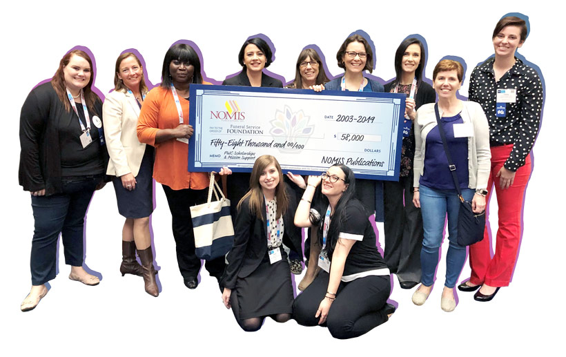 A diverse group of people holding up a large donation check from Nomis made out to the Funeral Service Foundation